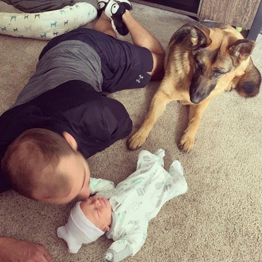 Mike Over kisses his son, Noah James Over, while the family German shepherd, Brea, watches. Noah was born on April 9.