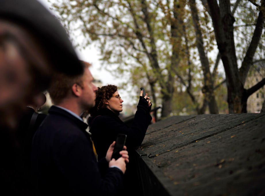 People gather to watch the Notre Dame cathedral after the fire in Paris, Tuesday, April 16, 2019. A catastrophic fire engulfed the upper reaches of Paris' soaring Notre Dame Cathedral as it was undergoing renovations Monday, threatening one of the greatest architectural treasures of the Western world as tourists and Parisians looked on aghast from the streets below. (AP Photo/Kamil Zihnioglu)