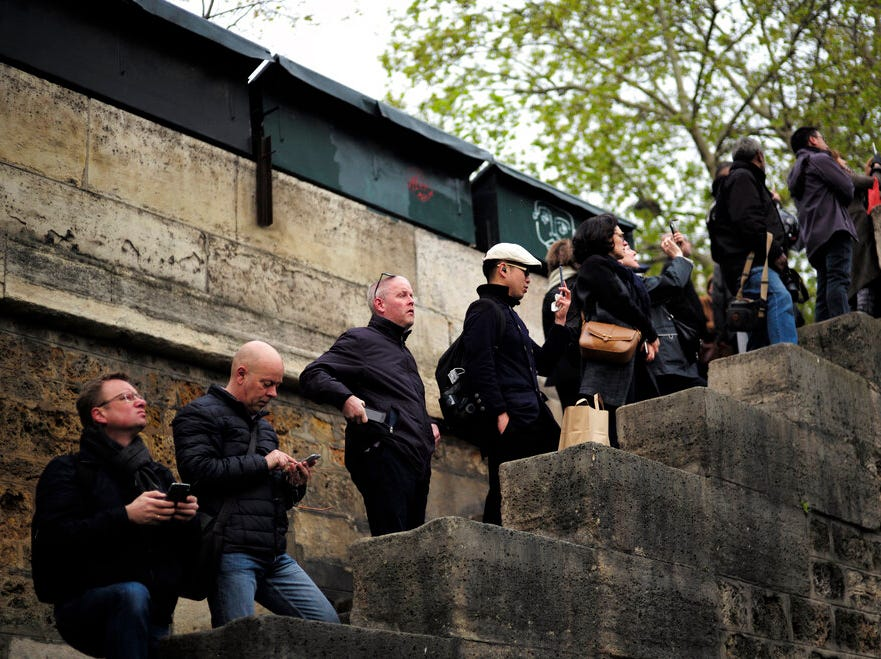 People stand to watch and photograph the Notre Dame cathedral after the fire in Paris, Tuesday, April 16, 2019. Experts are assessing the blackened shell of Paris' iconic Notre Dame cathedral to establish next steps to save what remains after a devastating fire destroyed much of the almost 900-year-old building. With the fire that broke out Monday evening and quickly consumed the cathedral now under control, attention is turning to ensuring the structural integrity of the remaining building. (AP Photo/Kamil Zihnioglu)