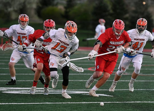 Logan Pauluch of Central York (13) and Susquehannock's Daniel Clapp chase down a loose ball, Monday, April 15, 2019.