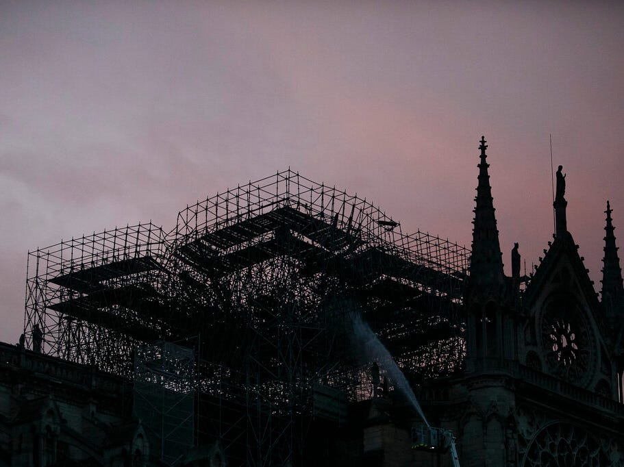 The Notre Dame cathedral is seen on sunrise as firefighters operate after the fire in Paris, Tuesday, April 16, 2019. A catastrophic fire engulfed the upper reaches of Paris' soaring Notre Dame Cathedral as it was undergoing renovations Monday, threatening one of the greatest architectural treasures of the Western world as tourists and Parisians looked on aghast from the streets below. (AP Photo/Kamil Zihnioglu)