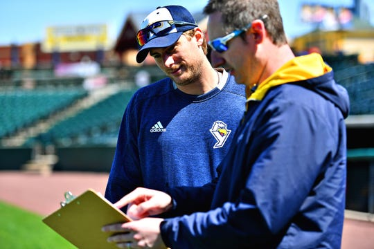 York Revolution play-by-play broadcaster Darrell Henry, right looks at the roster with pitcher Ross Detwiler during a practice at PeoplesBank Park in York City, Tuesday, April 16, 2019. Detwiler is one of the key returning players for the Revs this season. Dawn J. Sagert photo