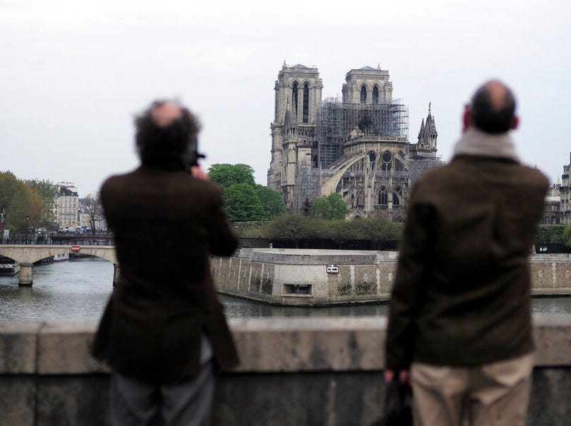 People stop to see and photograph the Notre Dame cathedral after the fire in Paris, Tuesday, April 16, 2019. Experts are assessing the blackened shell of Paris' iconic Notre Dame cathedral to establish next steps to save what remains after a devastating fire destroyed much of the almost 900-year-old building. With the fire that broke out Monday evening and quickly consumed the cathedral now under control, attention is turning to ensuring the structural integrity of the remaining building. (AP Photo/Kamil Zihnioglu)