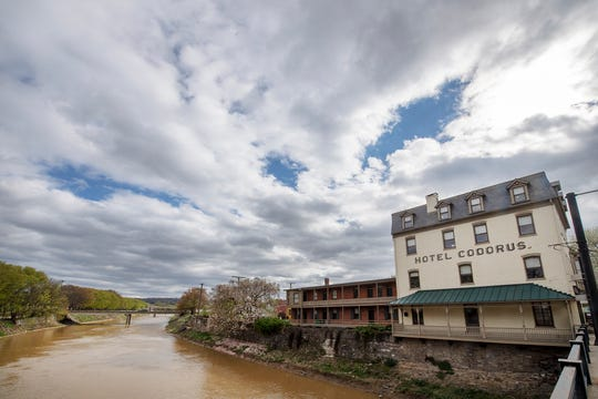 Looking from West Market Street, the swollen Codorus Creek flows past the former Hotel Codorus after a heavy spring rain.