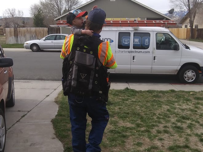 Fletcher Hulsey shows off his work truck to 2-year-old Arlo Gelsone on a house call in Gardnerville.