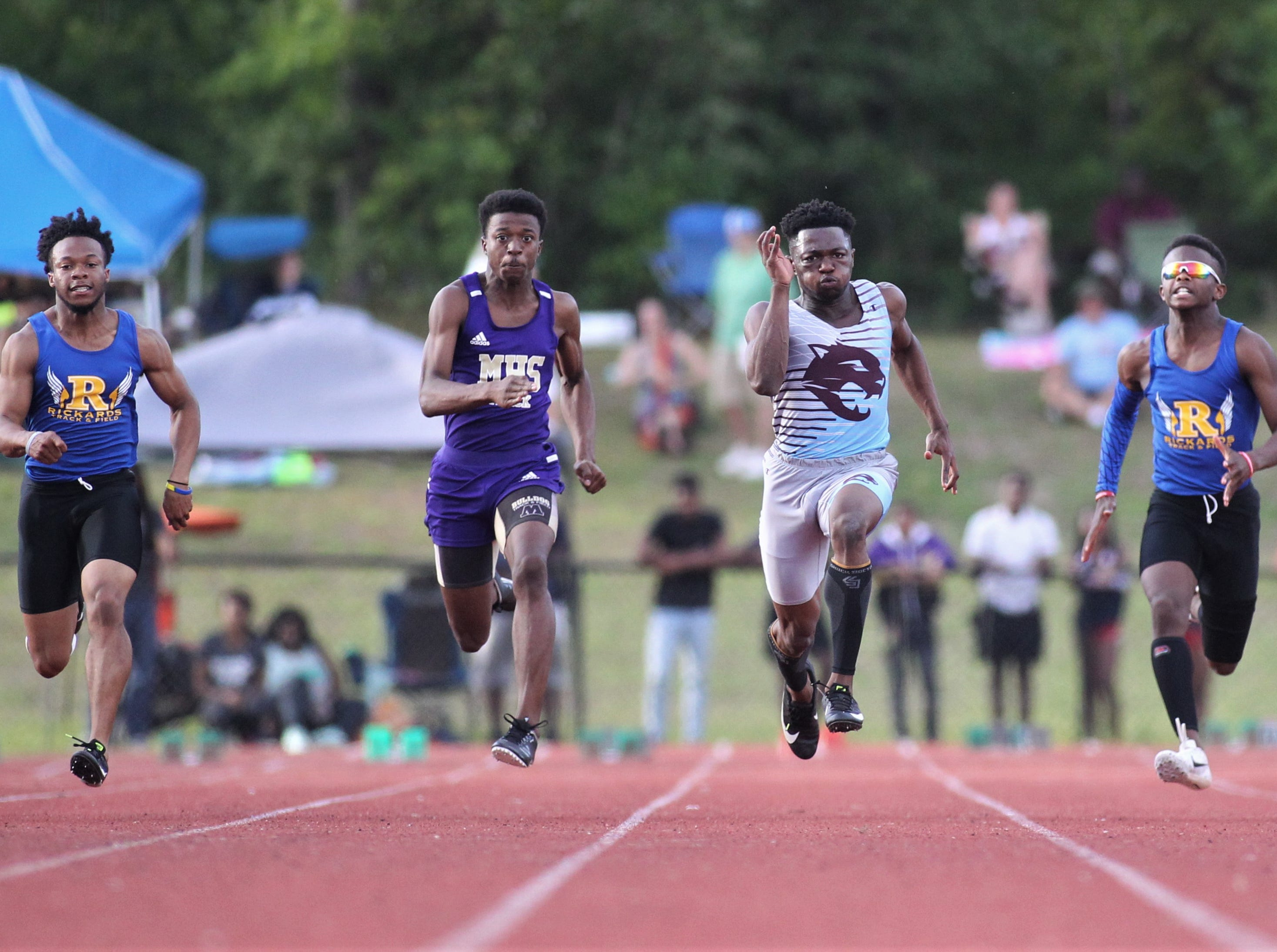 Gadsden County junior Dequavious Charleston (middle) sprints in the 100-meter dash during District 3-1A and 2-2A track and field meets at Florida High on Saturday, April 13, 2019.