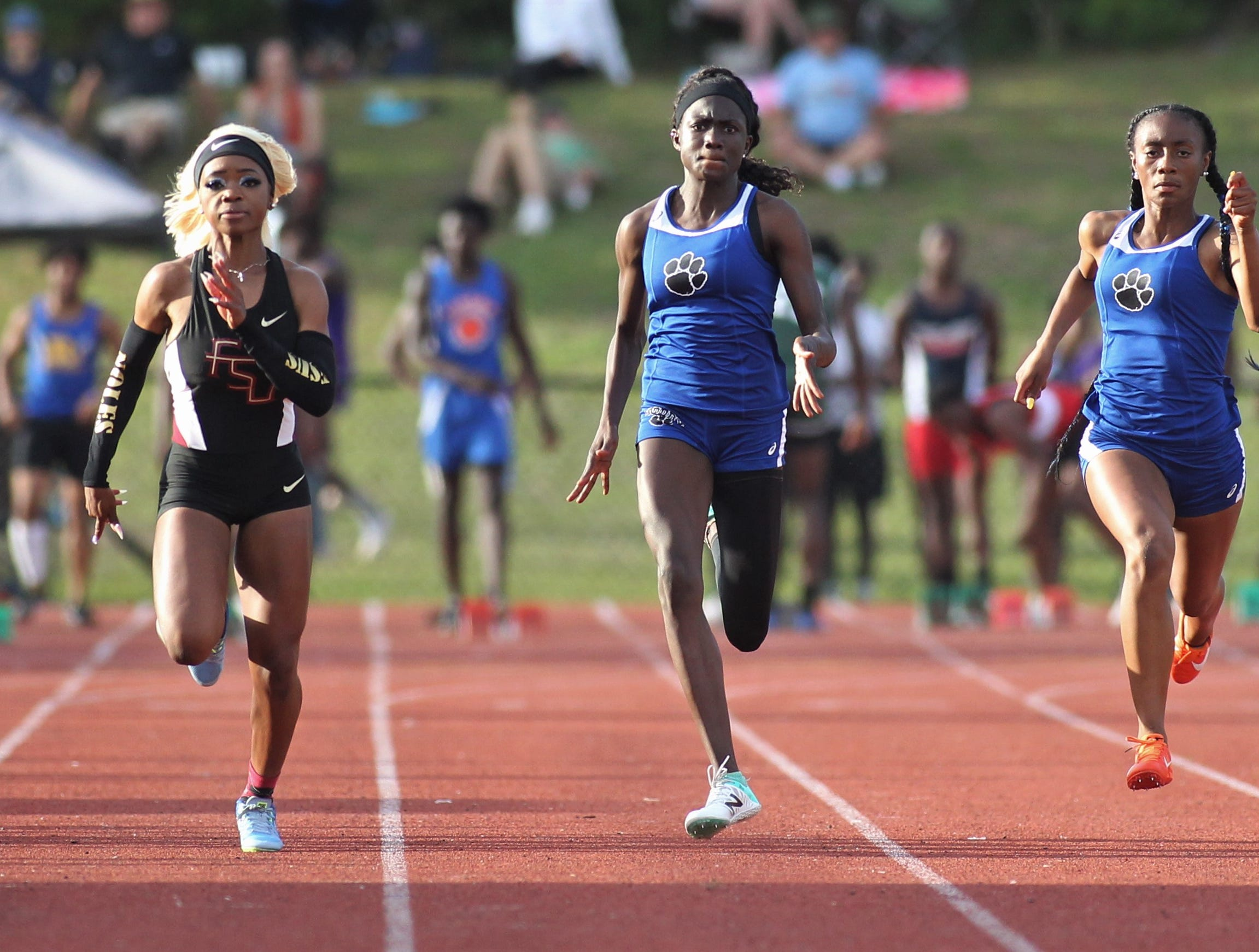 Godby's Naveyh Frost (middle) races next to Florida High junior Jacquell Lewis and Godby junior A'Kyrah O'Banner during District 3-1A and 2-2A track and field meets at Florida High on Saturday, April 13, 2019.