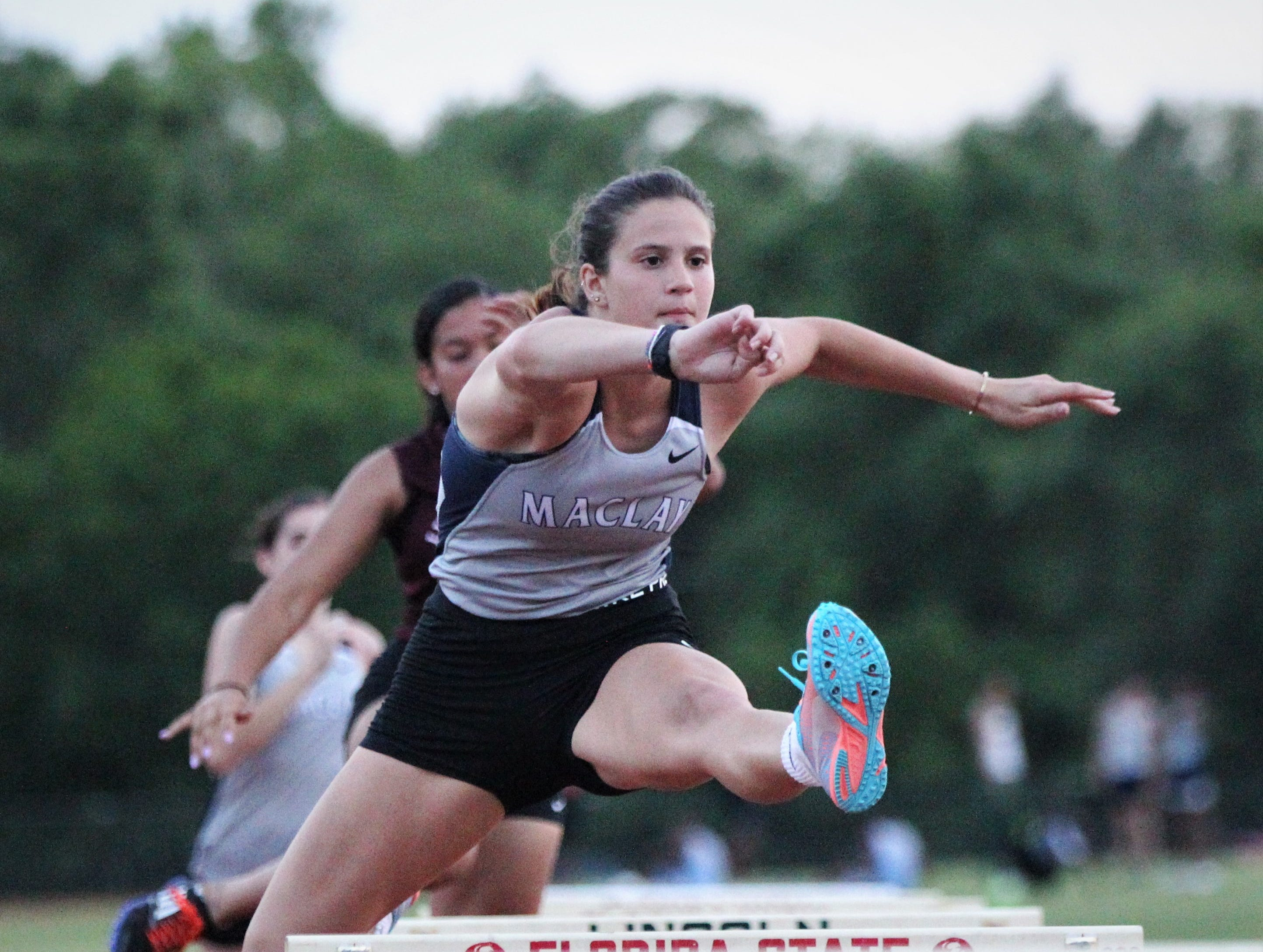Maclay senior Kenzie Mazziotta clears a hurdle during the District 3-1A and 2-2A track and field meets at Florida High on Saturday, April 13, 2019.
