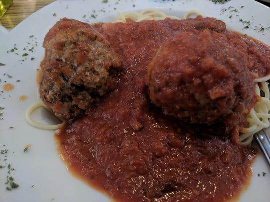 Spaghetti and two gigantic moist and flavorful meatballs are cooked in a spicy Italian red sauce at DeAngelo's By the Sea.