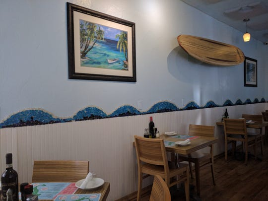 Inside DeAngelo's By The Sea, sea glass forms images of ocean waves above white beadboard and paintings  of sublime ocean scenes grace the walls.