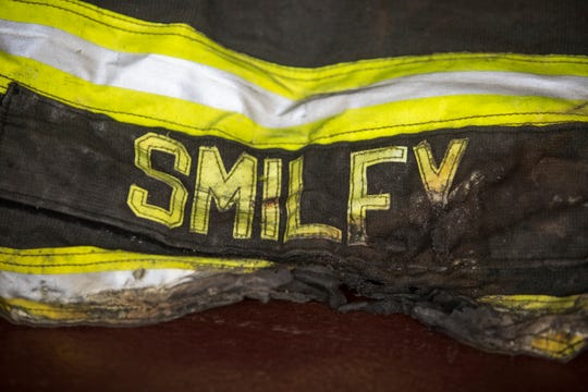 The name on the back of Dave Smiley's fireman's jacket was partially burned off when Smiley was trapped inside the second floor of a burning home last month in Mill Creek.