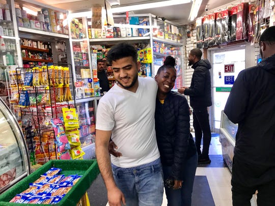 Bill's Deli Market worker Nas Elsamet hugs a local woman after the store is allowed to re-open
