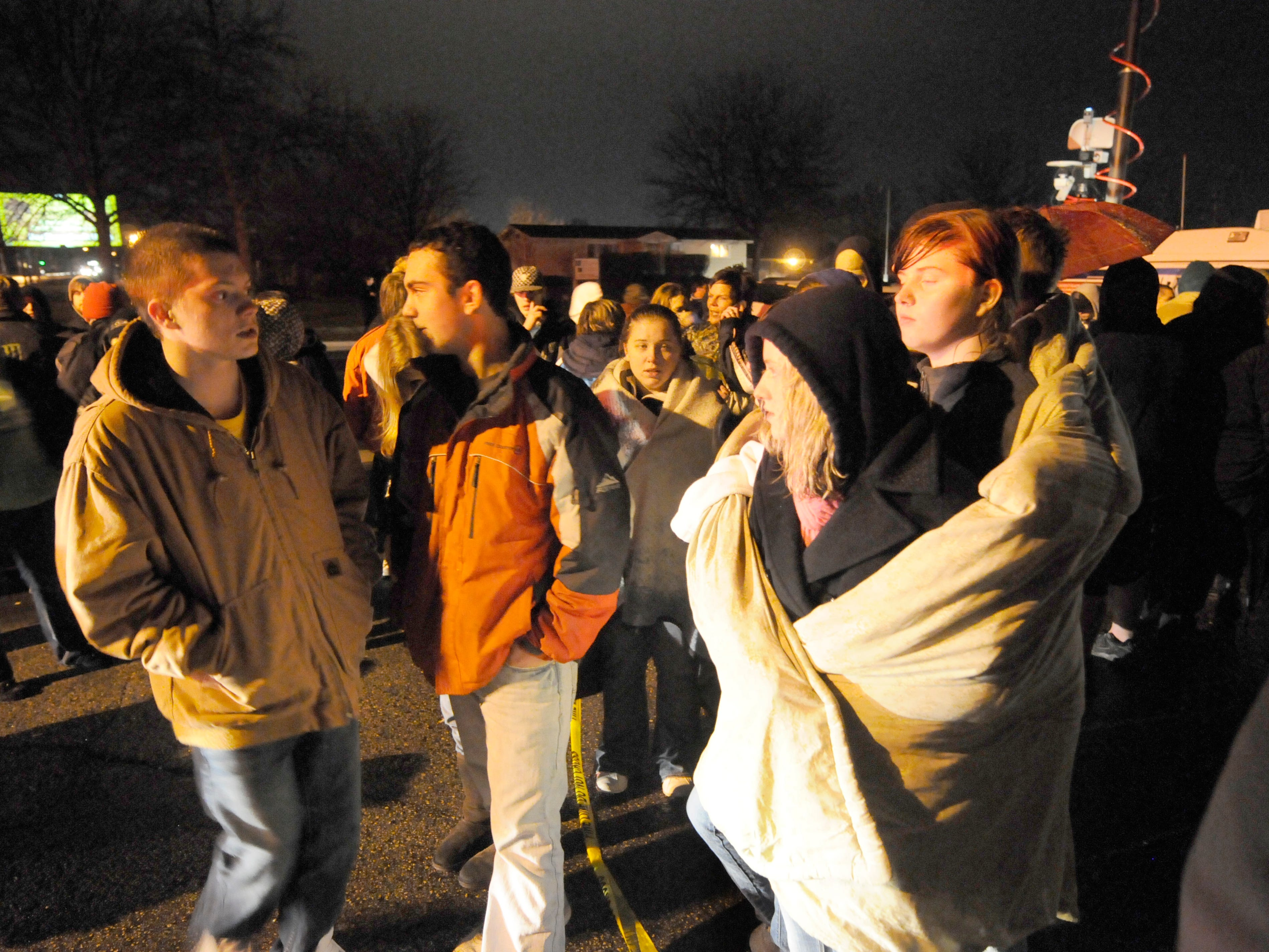 Marinette High School students hold a vigil in a parking lot near the school as they wait for word on the 23 hostages being held in Marinette Monday, November 29, 2010. Caitlin Peterson, right, huddles in the rain with Brittany Padgett. Jim Matthews/Press-Gazette