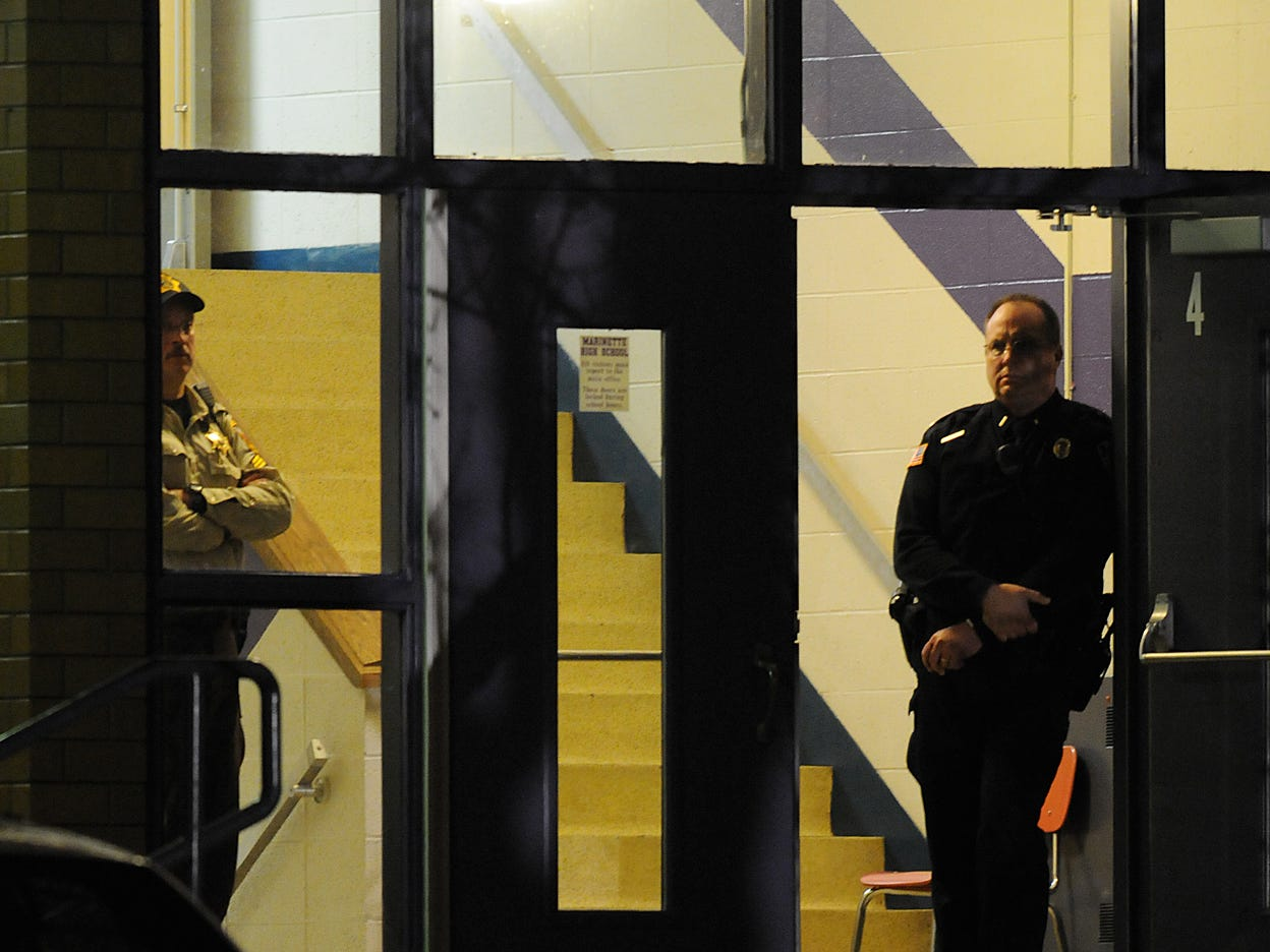 Law enforcement officers stand guard at an entrance to Marinette High School at 5:00 a.m. on Nov. 30, 2010 where a 15-year-old male held a classroom hostage at the school on Nov. 29 in Marinette, Wisconsin.  At one point police heard three gunshots from the classroom and entered where the suspect then shot himself with a handgun according to Marinette police chief Jeffery Skorik.  Photo by Corey Wilson/Press-Gazette