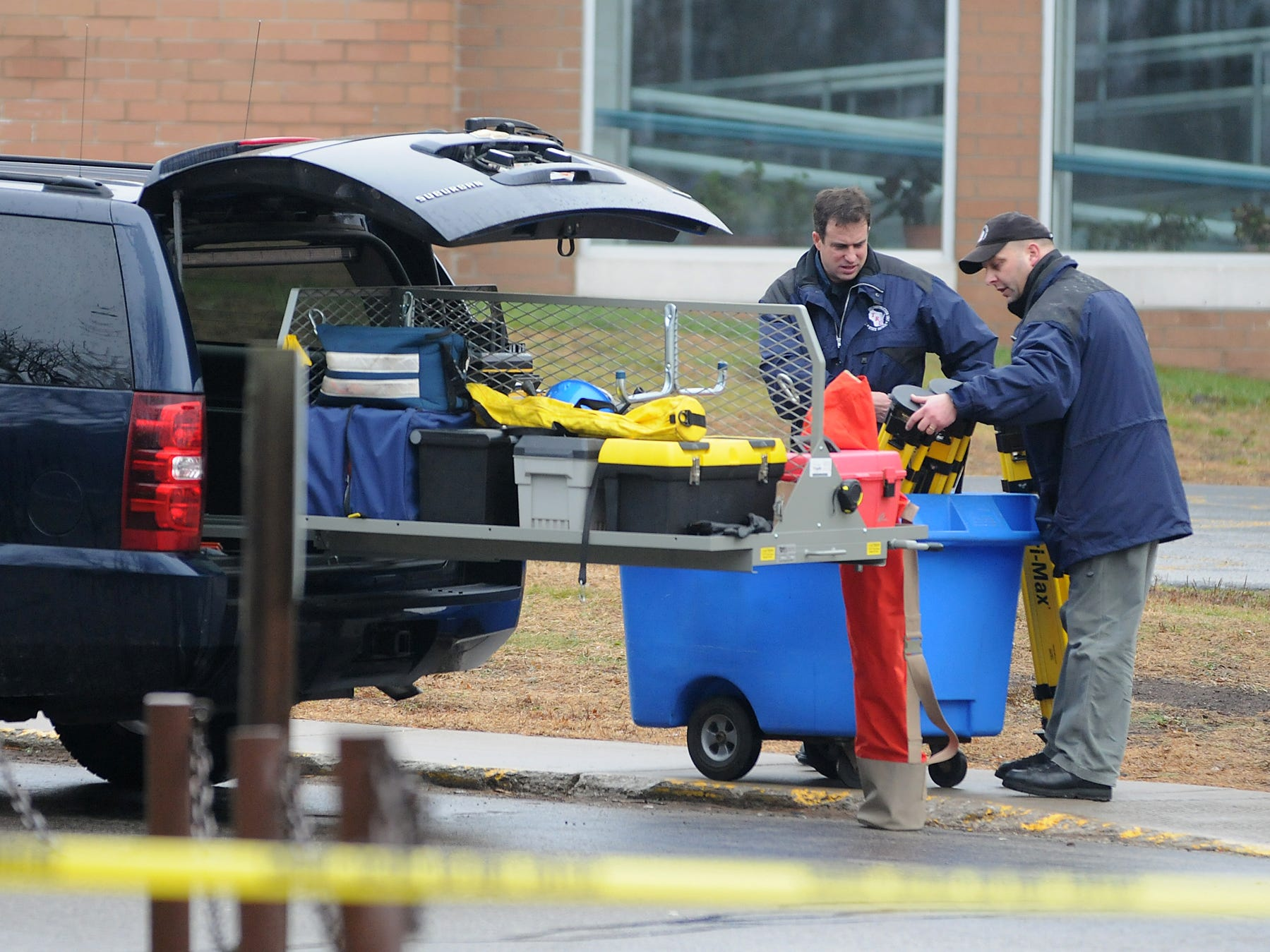 Investigators load a cart of equipment back into a vehicle after the gear was used during the investigation at Marinette High School on Nov. 30, 2010 following a hostage incident on Nov. 29 where a 15-year-old male held a classroom of students and a teacher in a classroomin Marinette, Wis., until police heard gunshots from the classroom, entered and the suspect shot himself with a handgun.  The incident occured in a classroom in the lower level of the school. Photo by Corey Wilson/Press-Gazette