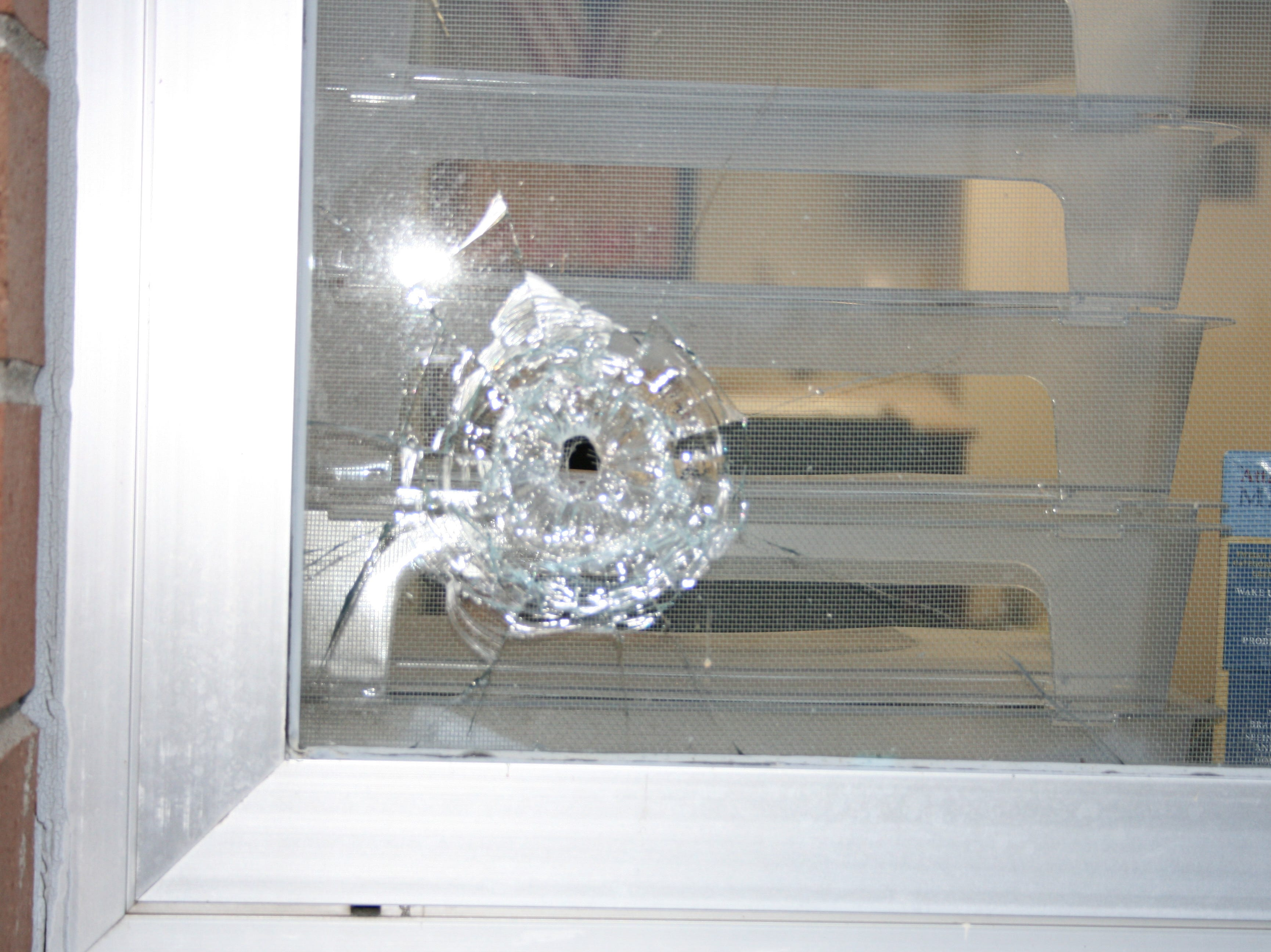 Bullet hole in a window at Marinette High School after the hostage taking incident on November 29, 2010. Provided by Marinette Police Department