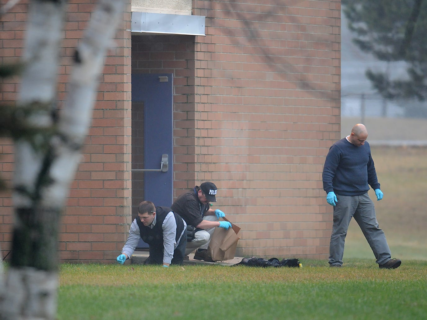 Police investigators gather, photograph and bag evidence outside a side entrance to Marinette High School just after 8:00 a.m. on Nov. 30, 2010 following a hostage incident on Nov. 29 where a 15-year-old male held a classroom of students and a teacher in a classroomin Marinette, Wis., until police heard gunshots from the classroom, entered and the suspect shot himself with a handgun.  Photo by Corey Wilson/Press-Gazette