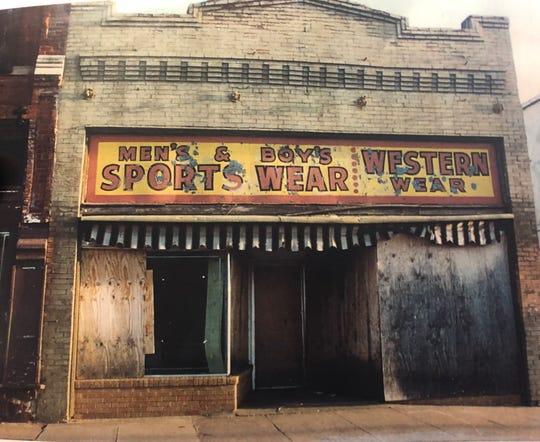 An image of 615 Seventh St., seen when it still had a red and yellow business sign. The building's owner wants to salvage and secure the remaining parts of the building even after the side wall and roof have collapsed.