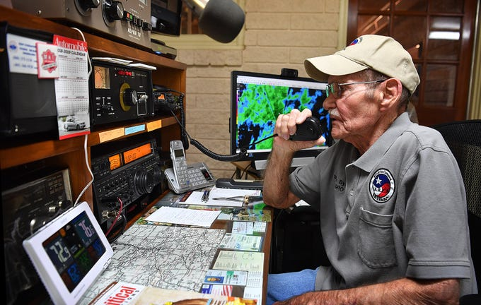 Ham radio operator Charlie Byars talks on his home radio setup to one of the weather spotters he helps coordinate through the Amateur Radio Emergency Service or A.R.E.S.