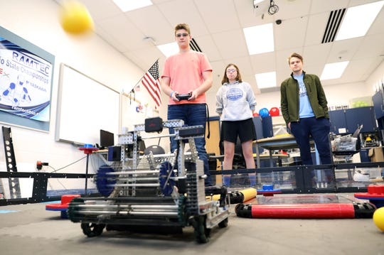 Zanesville High School robotics team members Alex Pinson, right, and Paige Jackson watch as driver Austin McCoy works with the team's robot in preparation for their trip to the VEX Robotics World Championship later this month.