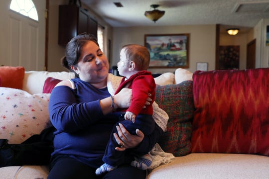 Jen Carter holds her foster son in their Zanesville home. Baby C was born  with Neonatal Abstinence Syndrome and Bronchopulmonary Dysplasia, requiring a feeding tube and breathing assistance.