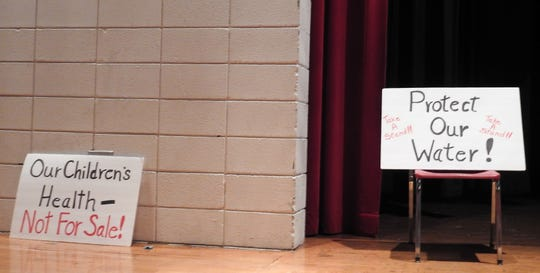 Signs protesting Buckeye Bring seeking new well permits from the Ohio Environmental Protection Agency on the stage of Coshocton High School during this week's public hearing.