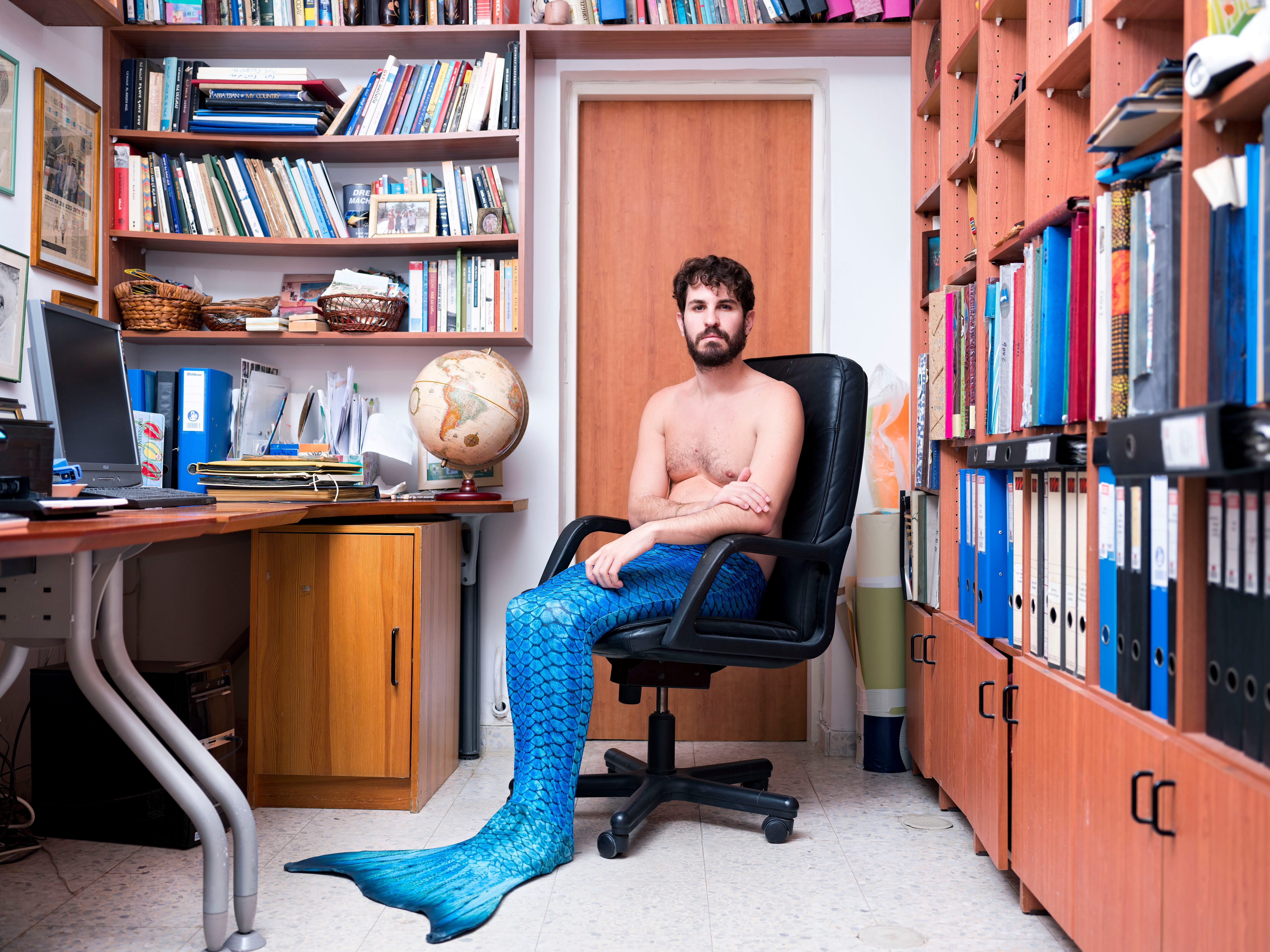 """In this Wednesday, Feb. 20, 2019 photo, Yuval Avrami, a member of the Israeli Mermaid Community, poses for a portrait as he wears a tail at his home in Jerusalem. One of the clan's few mer-men, says he learned about the trend through transgender friends and became fascinated by """"the transition from one species to another, the ability to inhabit a new, magical identity."""""""