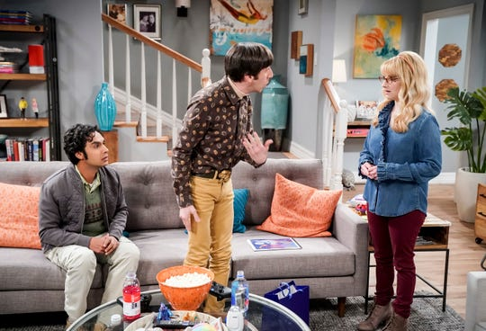 (Kunal Nayyar), on the left, listens as his friends, Howard's partners (Simon Helberg) and Brandt (Melissa Roach), discuss the episode of CBS The Big Bang theory.