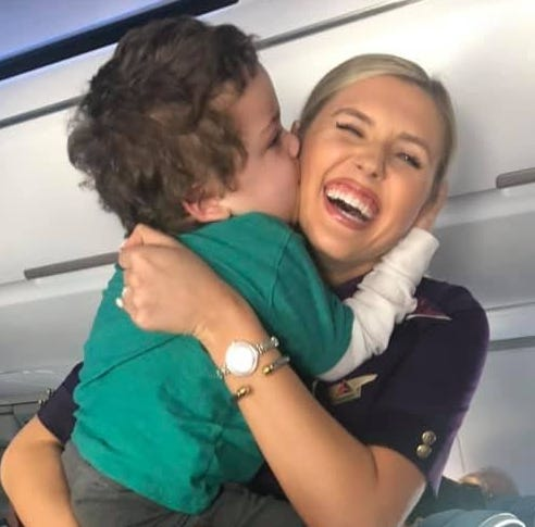Delta flight attendant Amanda Amburgy receives a hug and kiss from Xayvior Johnson.