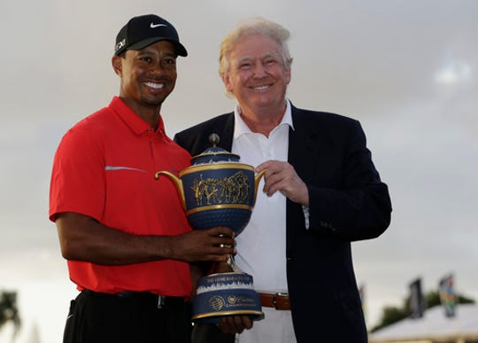 Tiger Woods stands with Donald Trump as he holds the Gene Serazen Cup for winning the Cadillac Championship golf tournament Sunday, March 10, 2013, in Doral, Fla.