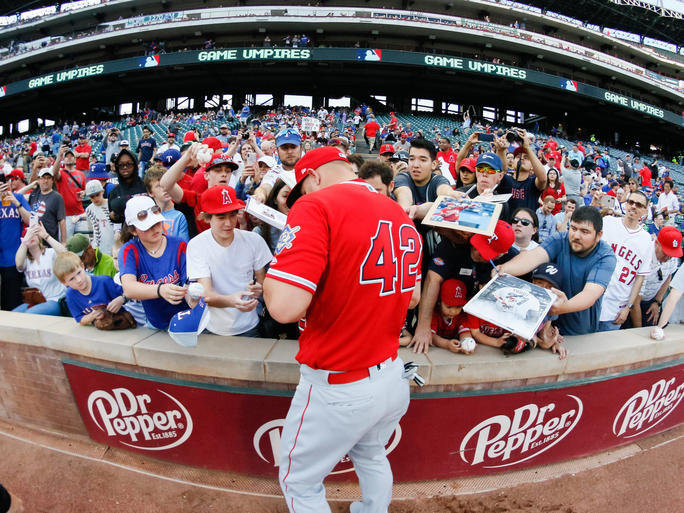 Angels center fielder Mike Trout, wearing No. 42, signs autographs.