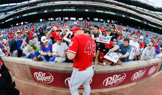 Angels center fielder Mike Trout, wearing No. 42, signs autographs. - Rays Pitcher Breaks Toe In Freak Accident