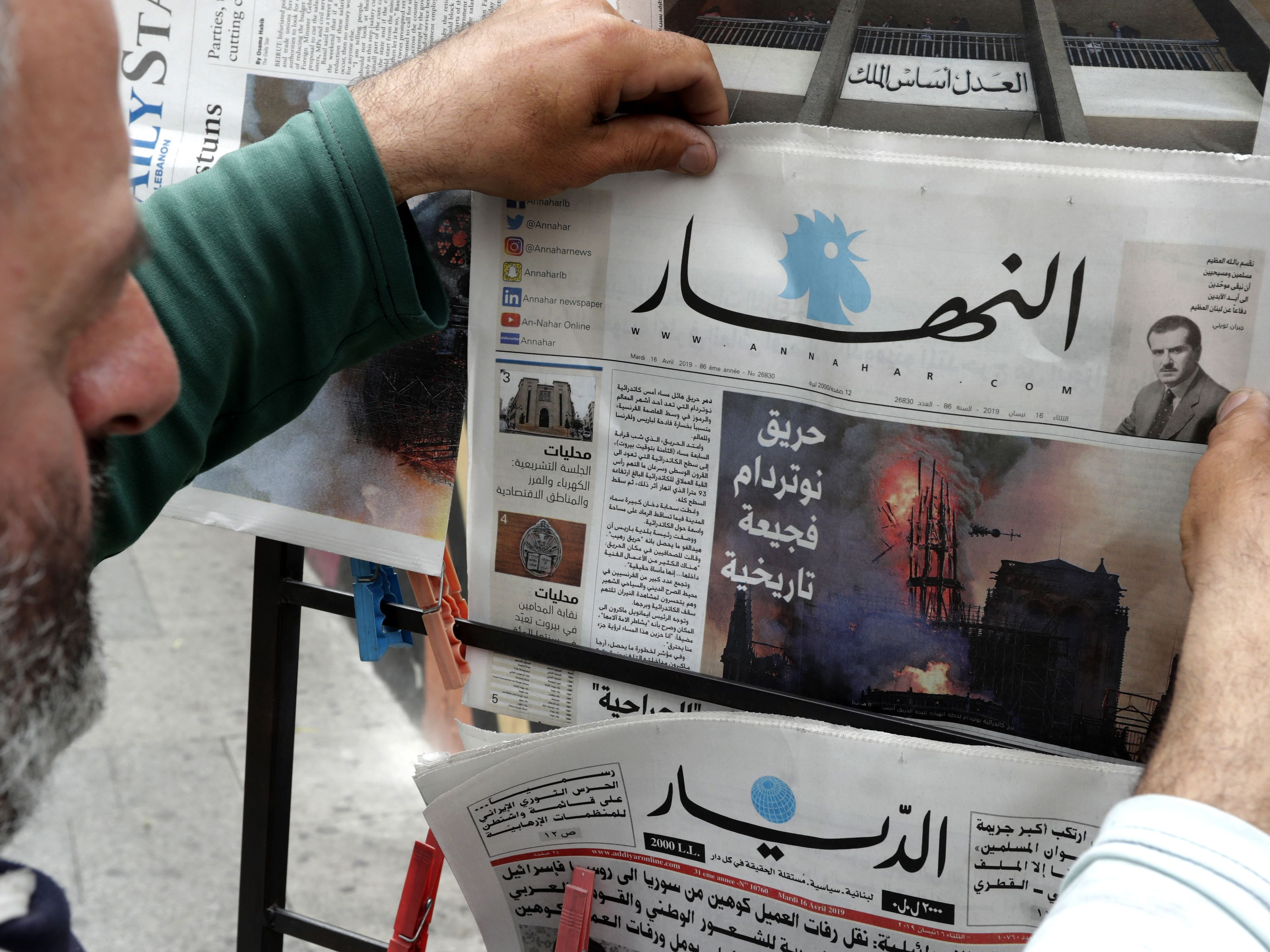 A man looks at the front page of the Lebanese Annahar newspaper, featuring on its front page an image of the fire that ravaged the Parisian Notre Dame cathedral, in the capital Beirut on April 16, 2019. - Paris was struck in its very heart as flames devoured the roof of Notre-Dame, the medieval cathedral made famous by Victor Hugo, its two massive towers flanked with gargoyles instantly recognisable even by people who have never visited the city. (Photo by ANWAR AMRO / AFP)ANWAR AMRO/AFP/Getty Images ORG XMIT: lebanon ORIG FILE ID: AFP_1FO6QP