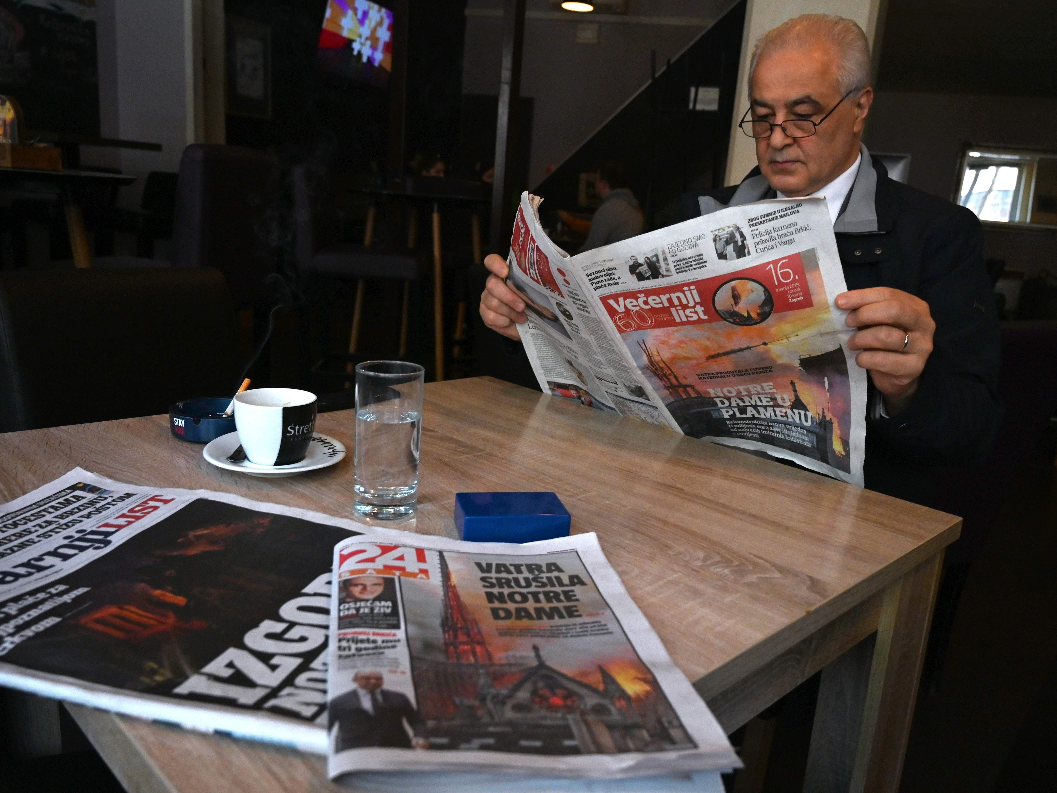 A Croatian man reads a daily newspapers with front page coverage of the Notre-Dame Cathedral fire in Paris, in Zagreb, on April 16, 2019.