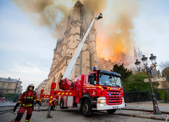 Fire fighters work at the burning Notre Dame cathedral, April 15, 2019.