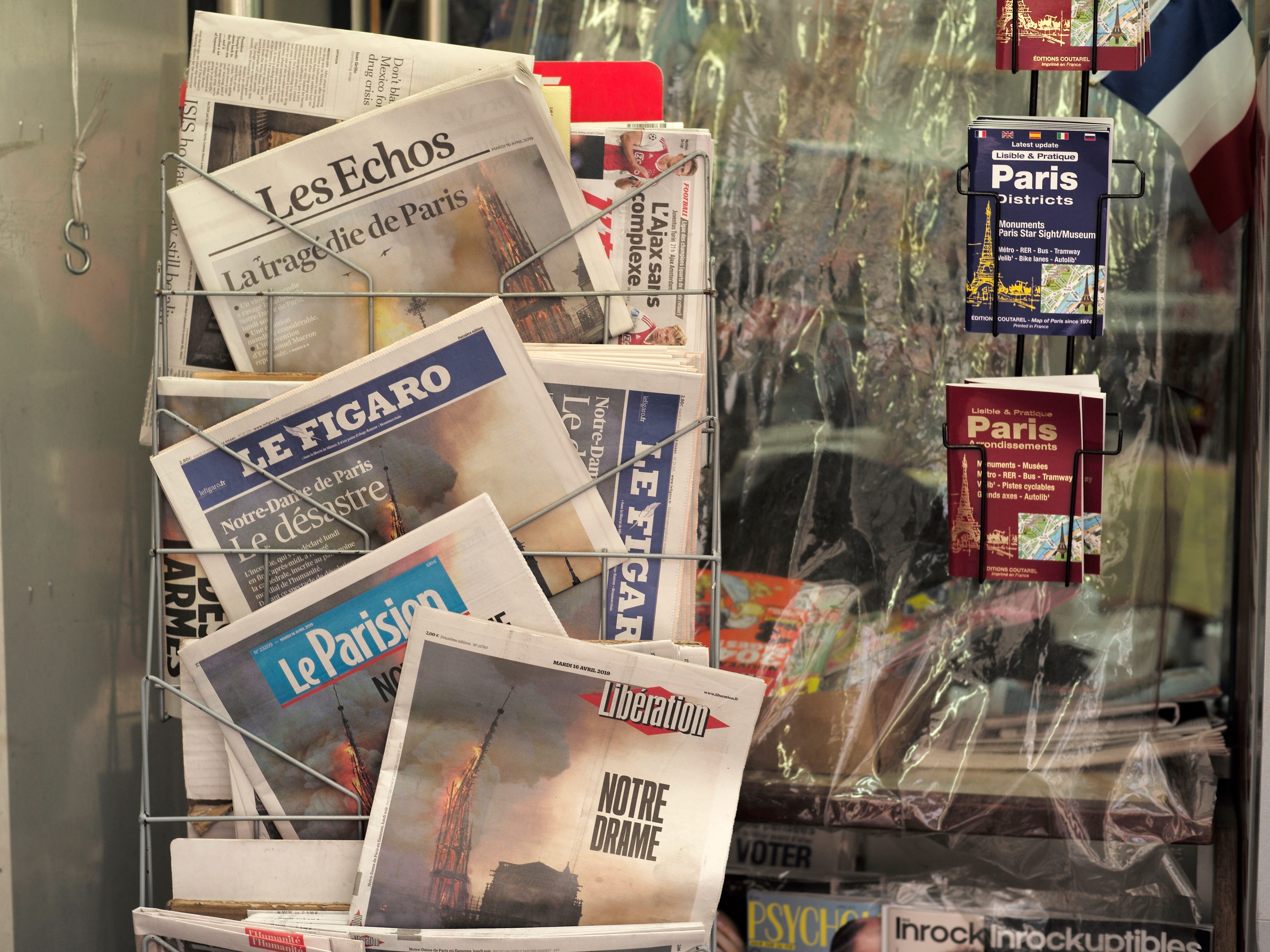 Front pages of newspapers show the Notre Dame cathedral in flames in Paris, April 16, 2019.