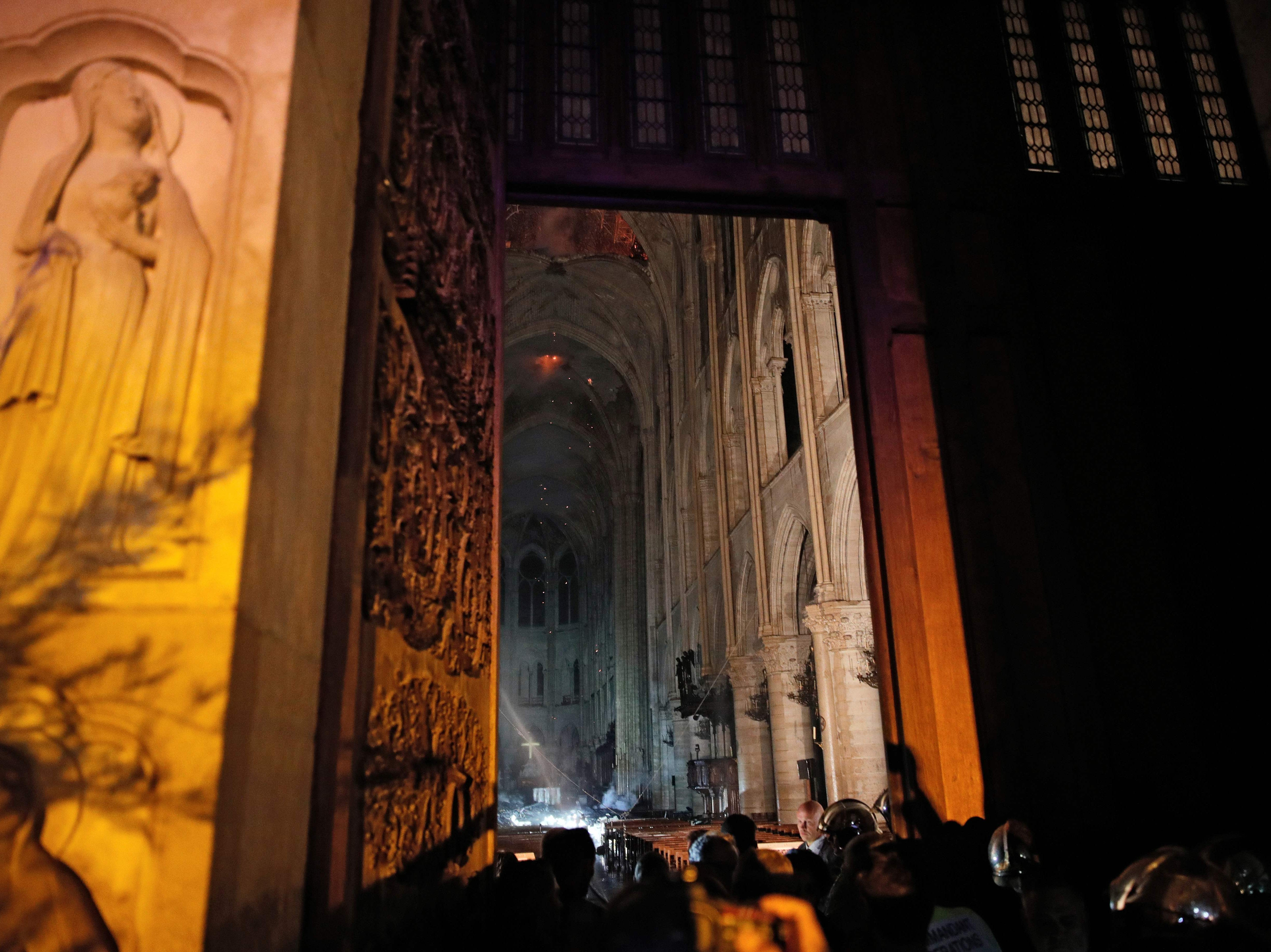 This general view from the entrance shows smoke rising in front of the altar cross at Notre Dame Cathedral on April 15, 2019.
