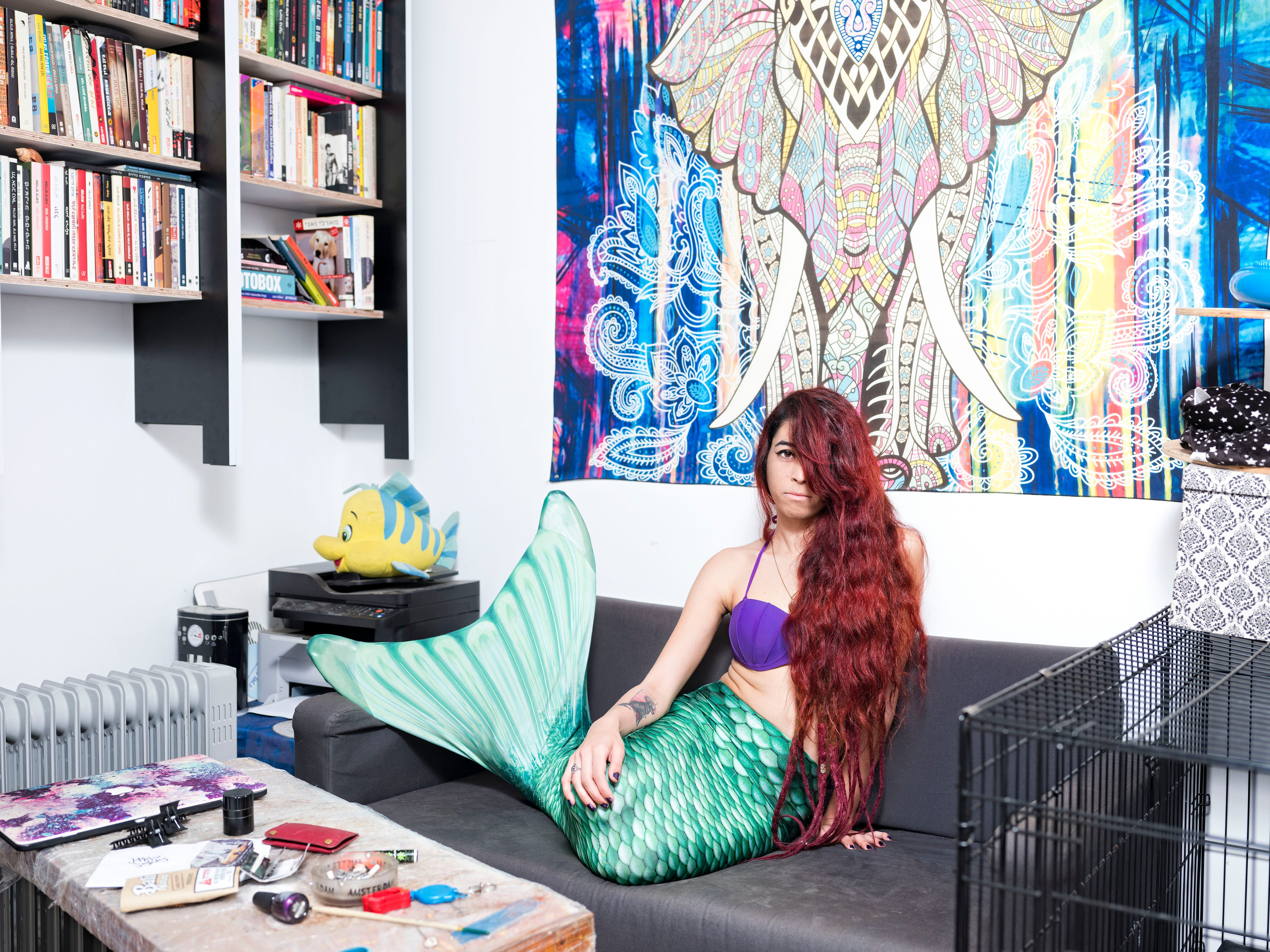 In this Sunday, Feb. 24, 2019 photo, May Lighty Cohen, a member of the Israeli Mermaid Community, poses for a portrait as she wears a mermaid tail at her home in Herzliya, Israel.