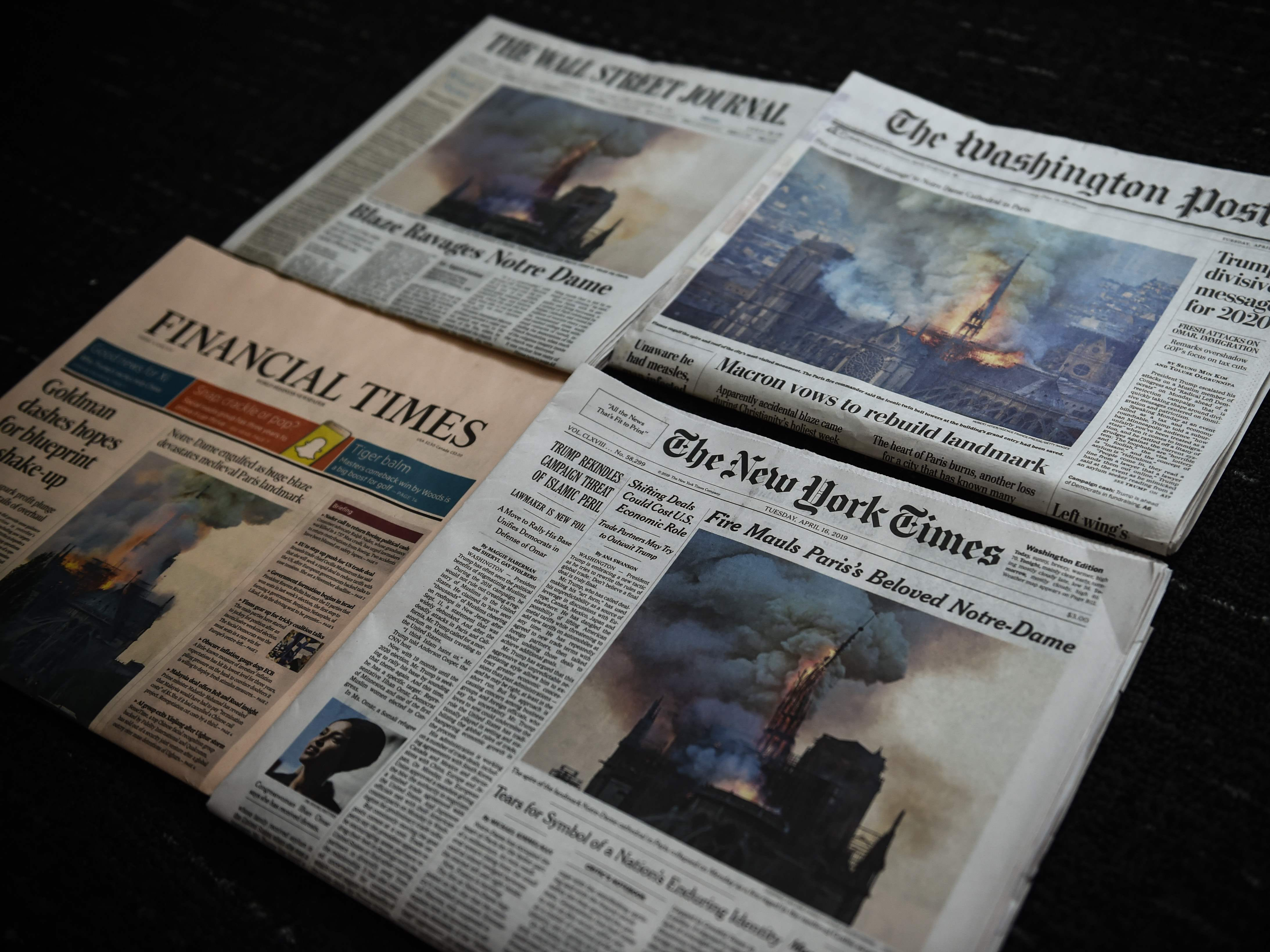 Editions of the New York Times, The Washington Post, The Wall Street Journal and the Financial Times display images of Notre-Dame Cathedral burning in Paris on their front page on April 16, 2019.