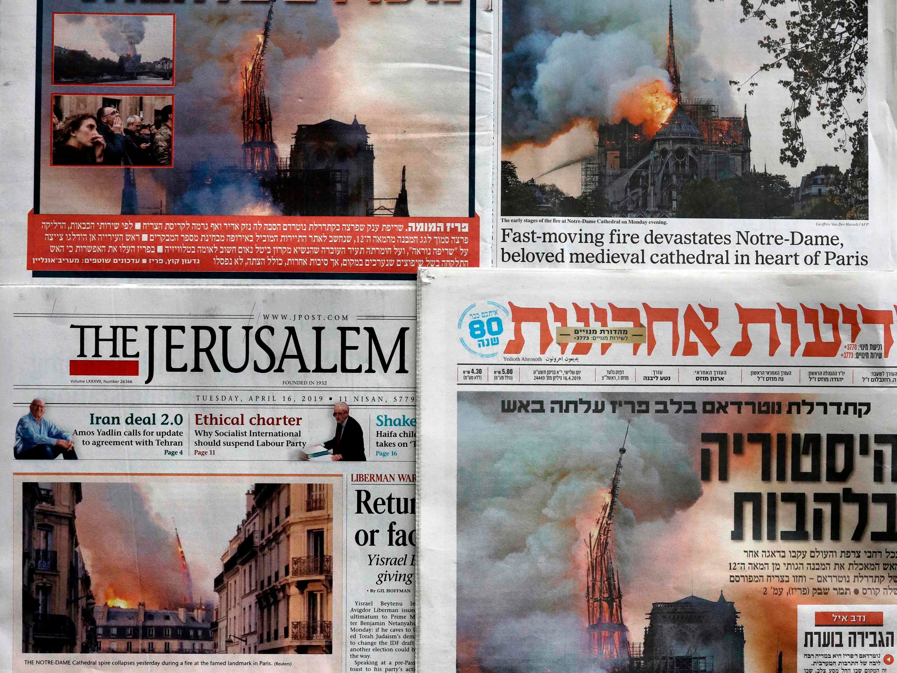 Israeli and Palestinian newspapers, featuring images of the fire that ravaged the Parisian Notre Dame cathedral on their front pages are seen in Jerusalem, on April 16, 2019.