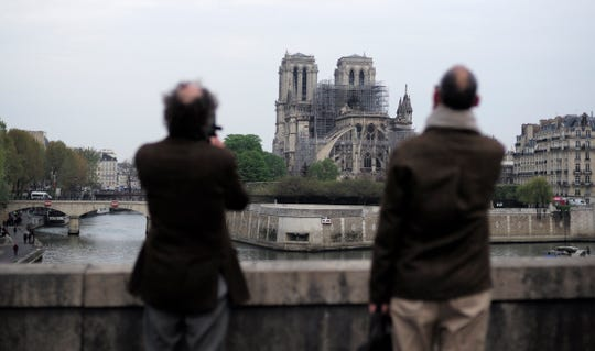 People stop to watch the Notre Dame Cathedral and photograph the fire in Paris, Tuesday, April 16, 2019. Experts rate the blackened shell of the famous Notre Dame Cathedral in Paris to take the next steps to save what's left after a devastating fire destroyed much of the nearly 900-year-old building. With the fire that broke out on Monday night and the cathedral quickly under control, it is important to ensure the structural integrity of the remaining building.