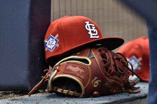 A Cardinals cap rests on the dug out wall with the No. 42 on the hat in honor of Jackie Robinson. - Rays Pitcher Breaks Toe In Freak Accident