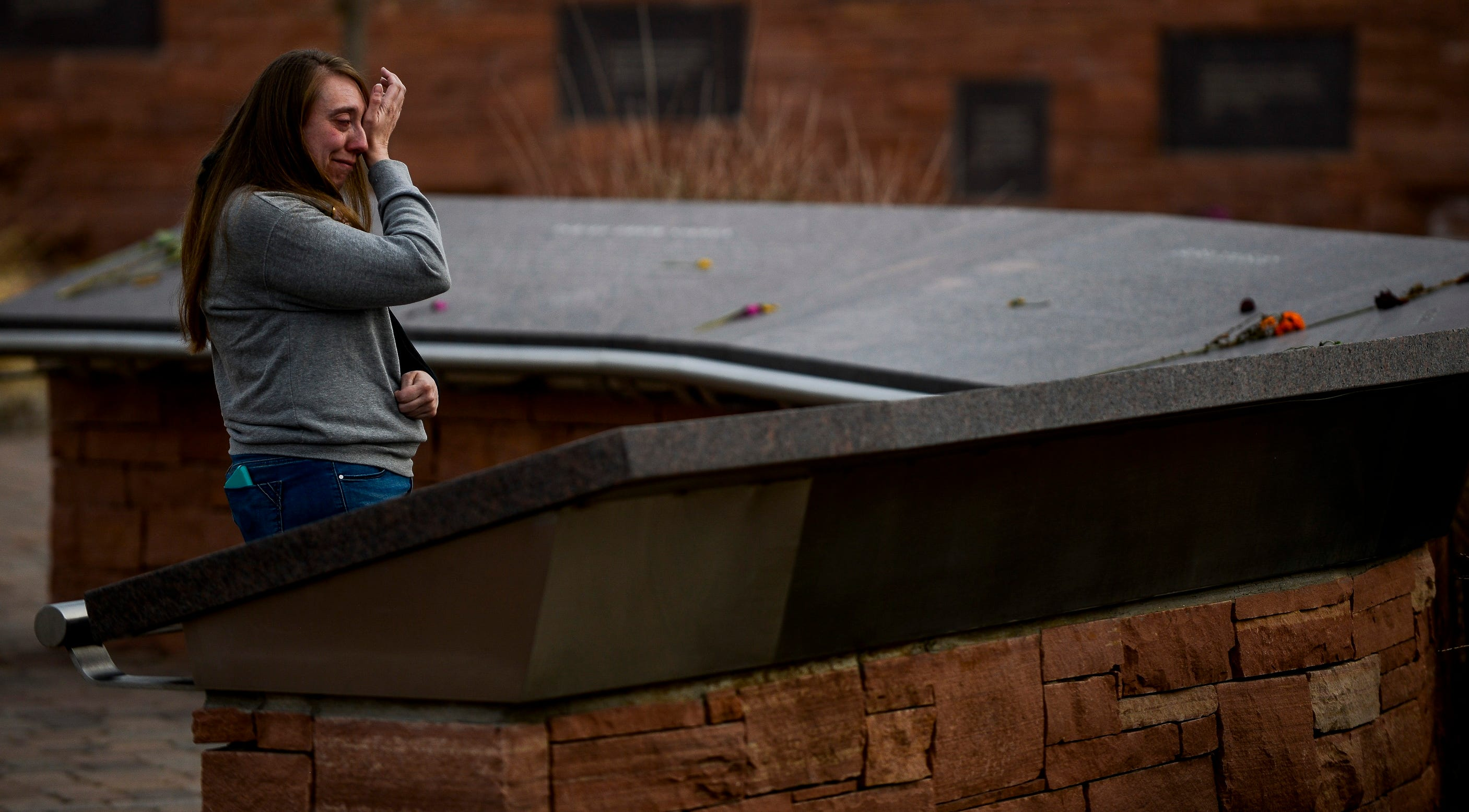 Nicole Boudreau, who was a freshman at Columbine High School during the 1999 mass shooting, wipes away a tears as she visits the Columbine Memorial in Littleton, Colo. on April 2, 2019.