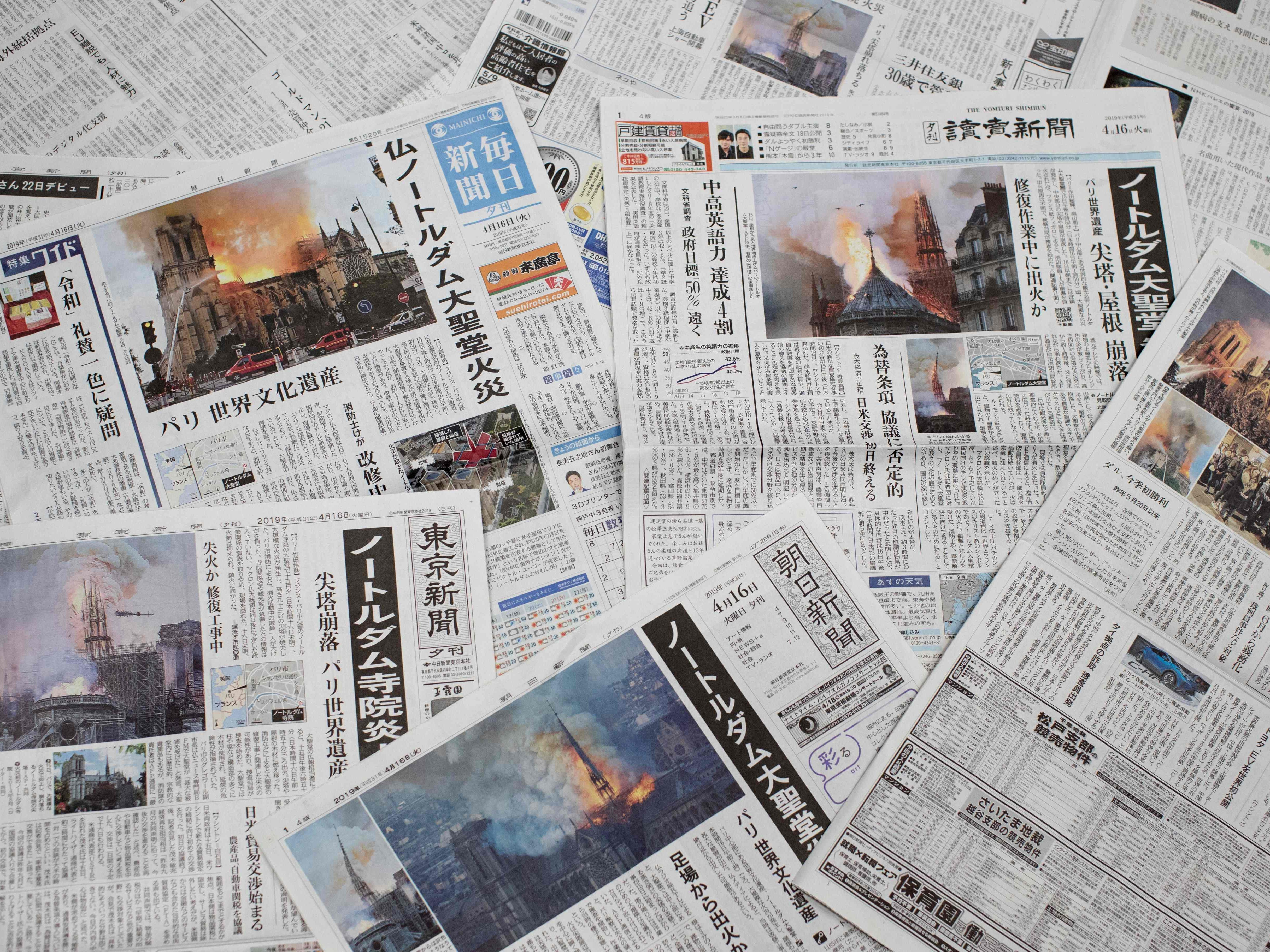 Japanese daily newspapers with front page coverage of the Notre-Dame Cathedral fire in Paris.