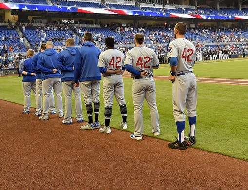Chicago Cubs players line up during the national anthem wearing the number 42 in honor of Jackie Robinson Day before a game against the Miami Marlins at Marlins Park. - Rays Pitcher Breaks Toe In Freak Accident