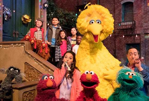 """This image released by HBO shows the cast of the popular children's show """"Sesame Street."""" Big Bird, Elmo and stars of """"Sesame Street"""" are leaving their quiet neighborhood and hitting the road. The non-profit Sesame Workshop said Tuesday a selection of Muppets will embark on a 10-city trip to celebrate the show's 50th anniversary campaign with free park festivals, live performances and kid-friendly activities."""