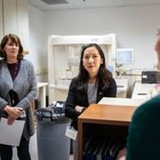 Leana Wen, president of Planned Parenthood, speaks with staff in a basement lab.