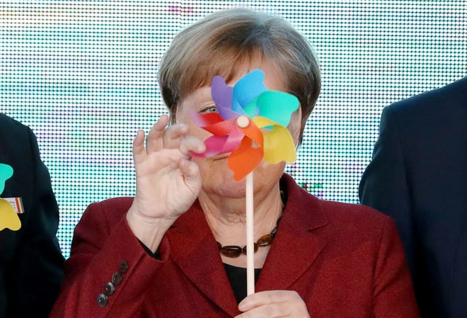 German Chancellor Angela Merkel holds an toy windmill, during an event officially launching an offshore wind park in the Baltic Sea near the island Ruegen, in Sassnitz-Mukran, Germany, Tuesday, April 16, 2019.