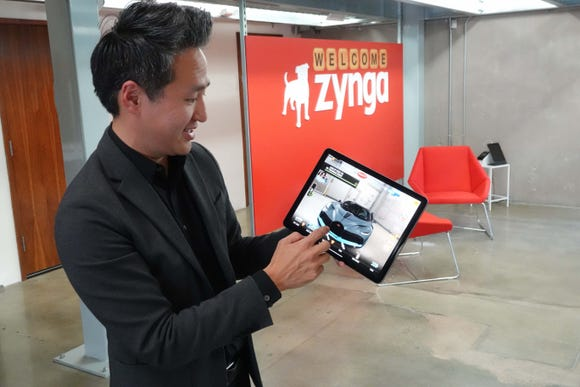 Zynga's Bernard Kim displays a Zynga racing game on an iPad
