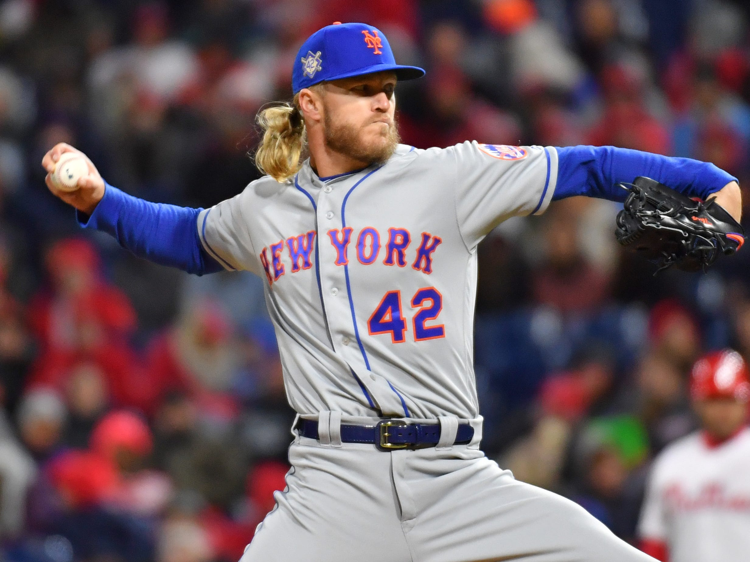 Mets starting pitcher Noah Syndergaard, wearing No. 42, throws a pitch.